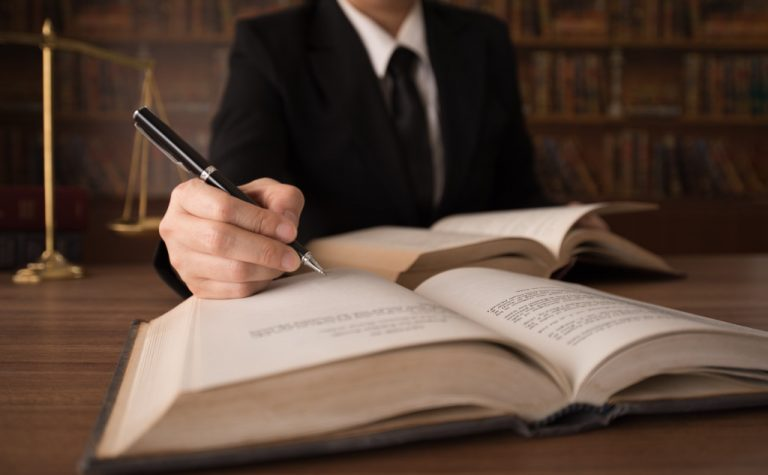 a person writing on a book of law